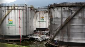 Trabajadores reparan un estanqe de la estatal brasileña Petrobras, en Cubatao, Brasil. 12 de abril de 2016. La producción de petróleo y gas natural de la compañía estatal brasileña Petrobras cayó en agosto un 1,42 por ciento frente a julio, luego de que la venta de activos en Argentina redujera la oferta internacional de la empresa. REUTERS/Paulo Whitaker