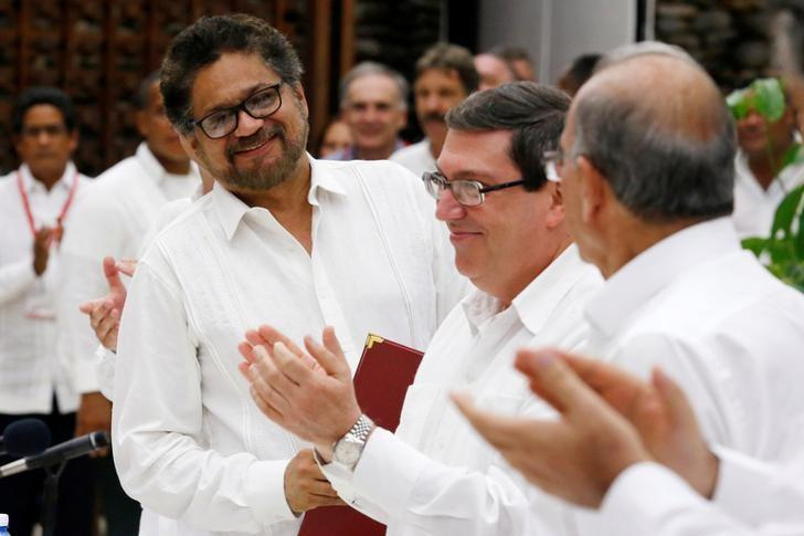 Colombia's FARC lead negotiator Ivan Marquez (L), Colombia's lead government negotiator Humberto de la Calle (R) and Cuba's Foreign Minister Bruno Rodriguez react after signing a final peace deal in Havana, Cuba, August 24, 2016. REUTERS/Stringer/File Photo