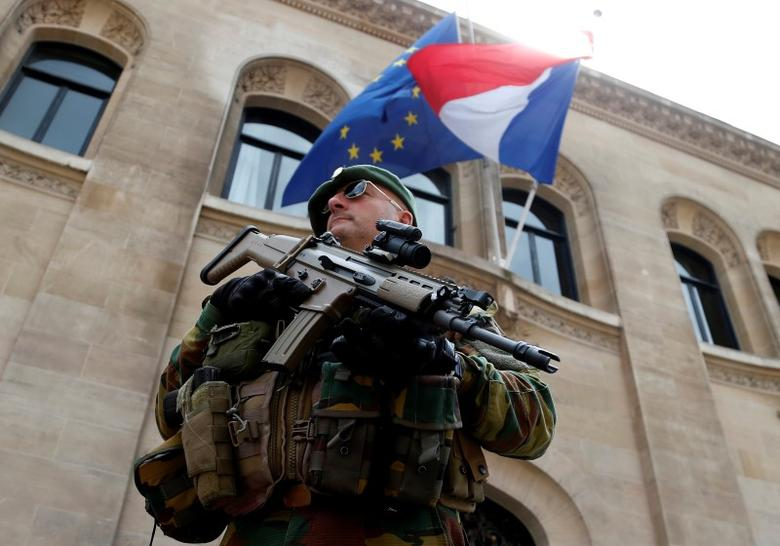 A Belgian soldier stands guard in front of the French embassy as French and European Union flags flutter at half staff to honor the victims of the Bastille Day truck attack in Nice, in Brussels, Belgium, July 15, 2016.  REUTERS/Francois Lenoir