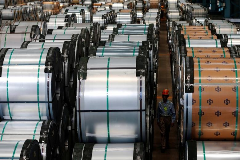 A worker walks past rolls of steel inside the China Steel Corporation factory, in Kaohsiung, southern Taiwan August 26, 2016. REUTERS/Tyrone Siu