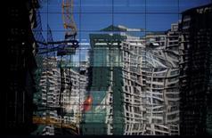 Uma obra e um prédio residencial refletidos em parede espelhada de edifício em Pequim. 15/12/2014 REUTERS/Kim Kyung-Hoon