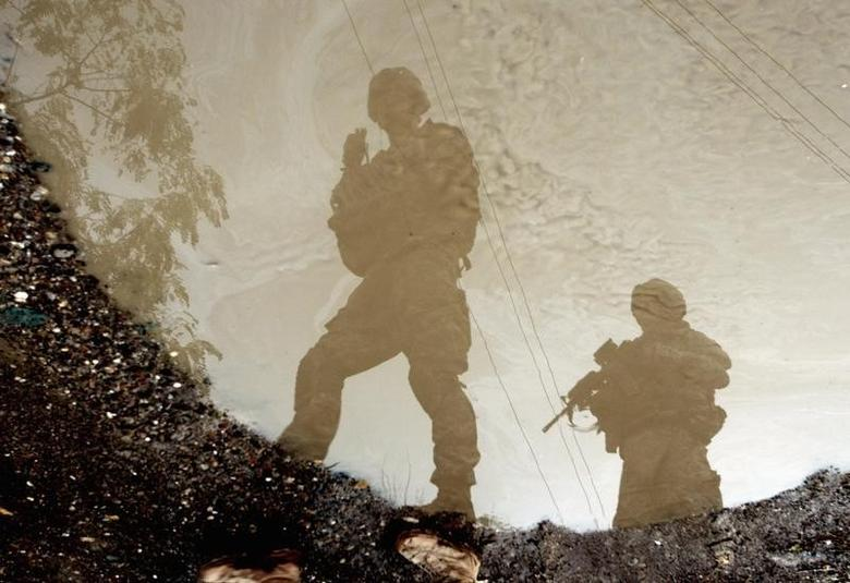 U.S. soldiers are reflected in a puddle as they patrol Baquba, in Diyala province, some 65 km (40 miles) northeast of Baghdad October 30, 2008. This photograph has been rotated 180 degrees. REUTERS/Goran Tomasevic (IRAQ)
