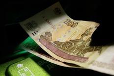 Клиент банкомата в отделении Сбербанка забирает из него деньги. Красноярск, 11 января 2016 года. Рубль подешевел во вторник, отразив снижение нефти и валют сырьевого и развивающегося сегментов форекса, но его негативную динамику сдерживала продажа экспортной выручки под предстоящие налоги, при этом рыночная активность и объемы были ниже средних значений в ожидании заседаний ЦБР и ФРС. REUTERS/Ilya Naymushin