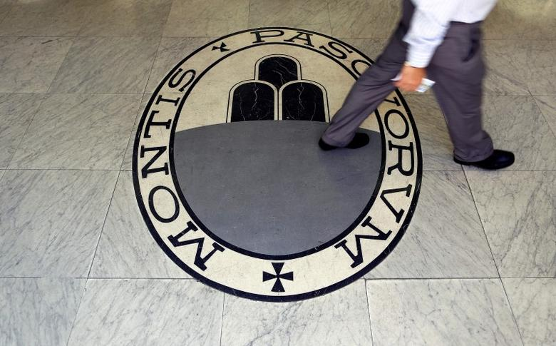A man walks on a logo of the Monte Dei Paschi Di Siena bank in Rome, Italy September 24, 2013. REUTERS/Alessandro Bianchi/File Photo - RTSHUXA