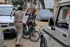Policial levantando bastão contra homem em Bangalore.   13/09/2016         REUTERS/Abhishek N. Chinnappa