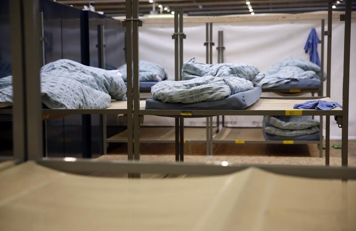 Bunk beds stand in a sleeping room in a Swiss Federal refugee center, set-up in a tank hall on the army base in Thun, Switzerland March 22, 2016. REUTERS/Ruben Sprich/File Photo
