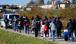 Мигранты следуют за полицейской машиной в регистрационный центр в Германии после пересечения границы со стороны Австрии в районе Вегшайд рядом с Пассау 1 ноября 2015 года. Главы крупнейших компаний Германии встретятся в среду с канцлером Ангелой Меркель, чтобы разъяснить, почему наняли менее сотни беженцев, тогда как за год в страну приехало около миллиона. REUTERS/Michael Dalder