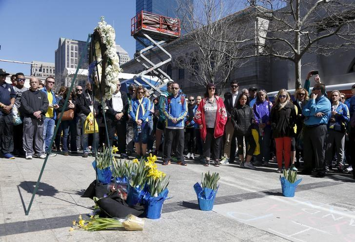 People gather for a moment of silence at one of the sites of the Boston Marathon bombings on Boylston Street in Boston, Massachusetts April 15, 2016. REUTERS/Mary Schwalm/File Photo