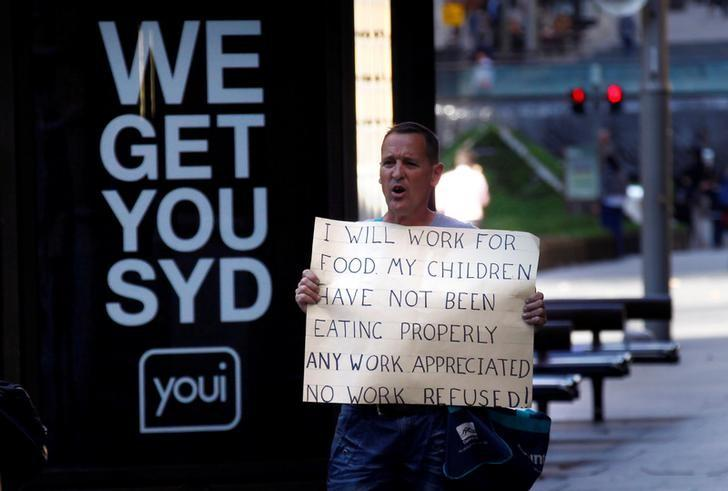 An unemployed man holds a sign asking for work as he stands on a footpath in central Sydney September 10, 2014.   REUTERS/David Gray/File Photo