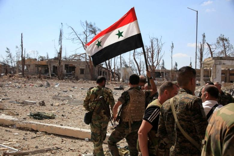 Forces loyal to Syria's President Bashar al-Assad walk at a military complex as one of them holds up a Syrian national flag, after they recaptured areas in southwestern Aleppo on Sunday that rebels had seized last month, Syria, in this handout picture provided by SANA on September 5, 2016. SANA/Handout via REUTERS/File Photo