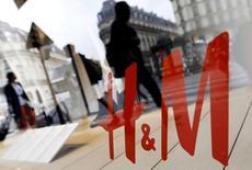 Люди идут мимо магазина H&M в Париже. Шведский ритейлер одежды и аксессуаров Hennes & Mauritz отчитался о росте продаж в августе, оказавшемся почти в два раза ниже ожиданий аналитиков, и сообщил, что непривычно жаркая погода на ключевых рынках привела к снижению числа покупателей во второй половине месяца. REUTERS/Regis Duvignau/File Photo