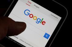 Мужчина держит смартфон с открытой поисковой страницей Google. Apple Inc и Google, принадлежащая Alphabet Inc, совершают действия, которые подрывают конкуренцию на рынке приложений для смартфонов, сообщила в четверг комиссия экспертов при министерстве экономики торговли и промышленности Японии. REUTERS/Regis Duvignau