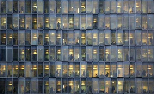 Lights are on as people work in their offices in a skyscraper in downtown Milan, February 17, 2015. REUTERS/Stefano Rellandini