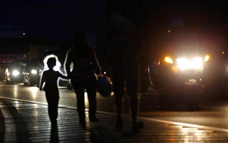 Migrants walk in the night along the highway towards the border with Austria, some 22 km of Budapest, Hungary, September 4, 2015. REUTERS/Laszlo Balogh