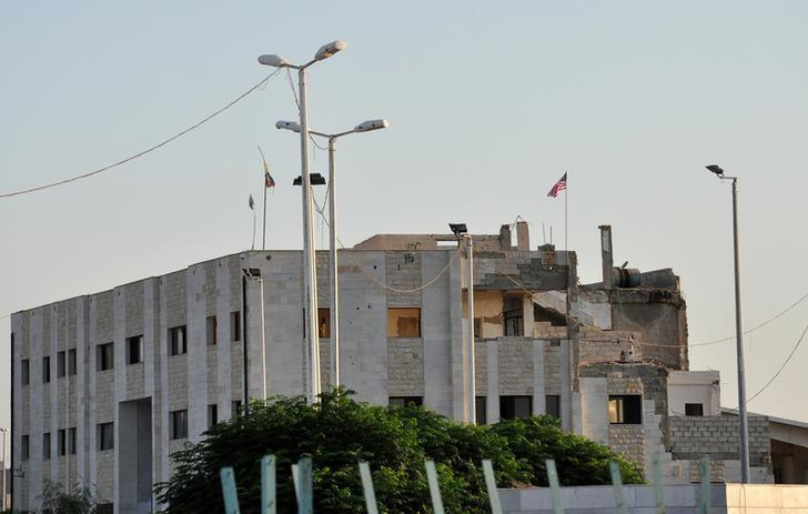 A national U.S. flag waves on top of a damaged customs building at the Syrian-Turkish border crossing of Tel Abyad, which is controlled by U.S.-allied Kurdish militia of the People's Protection Units (YPG), as it is seen from the Turkish border town of Akcakale in Sanliurfa province, Turkey, September 15, 2016. REUTERS/Kadir Celikcan/Files