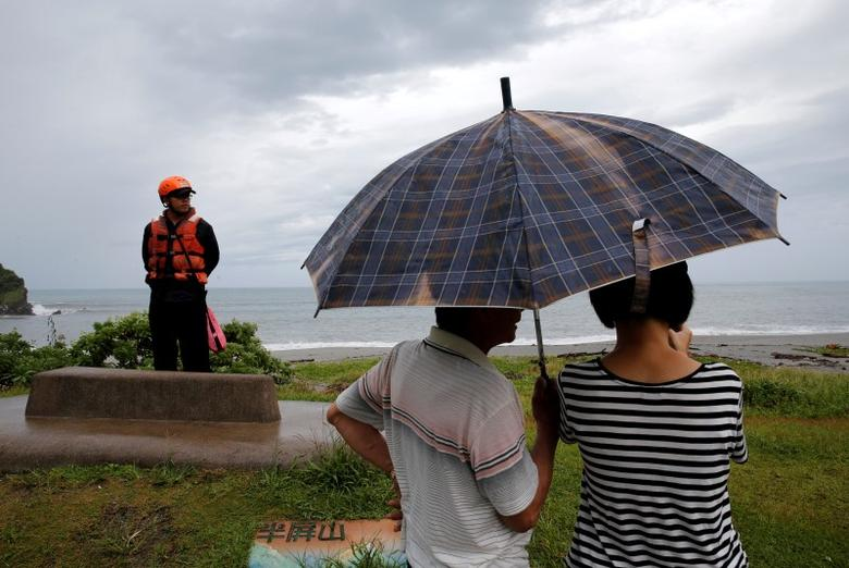 A coast guard stands guard at the coast as Typhoon Malakas approaches in Yilan, Taiwan September 17, 2016. REUTERS/Tyrone Siu