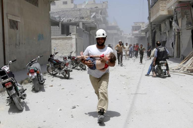 A civil defence member carries an injured girl at a site hit by airstrikes in the rebel-controlled area of Maaret al-Numan town in Idlib province, Syria. REUTERS/Khalil Ashawi