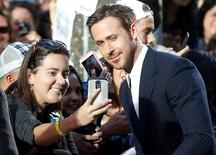 Actor Ryan Gosling greets fans as he arrives on the red carpet for the film La La Land. REUTERS/Mark Blinch