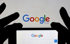 A woman holds her smart phone, which displays the Google home page, in this picture illustration taken February 24, 2016.  REUTERS/Eric Gaillard/Illustration/File Photo