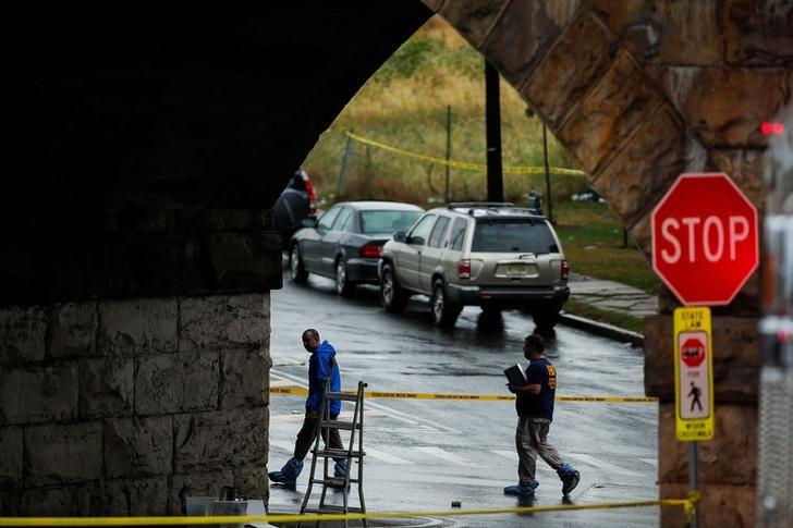 Federal Bureau of Investigation (FBI) officials walk near the area where an explosive device left at a train station was detonated by the authorities in Elizabeth, New Jersey, U.S., September 19, 2016. REUTERS/Eduardo Munoz