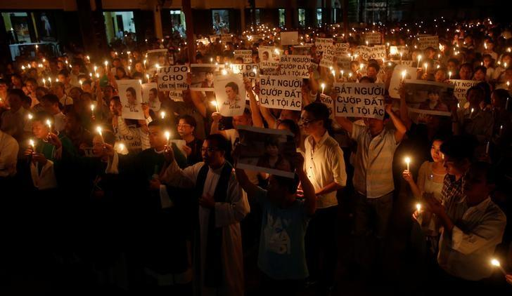 Participants hold images of dissident blogger Nguyen Huu Vinh and land protection activist Can Thi Theu during a mass prayer to call for justice in their trials at Thai Ha church in Hanoi, Vietnam  September 18, 2016. The signs read ''Freedom for Can Thi Theu'' and ''Make arrests - Grabbing land is criminal''.  REUTERS/Kham