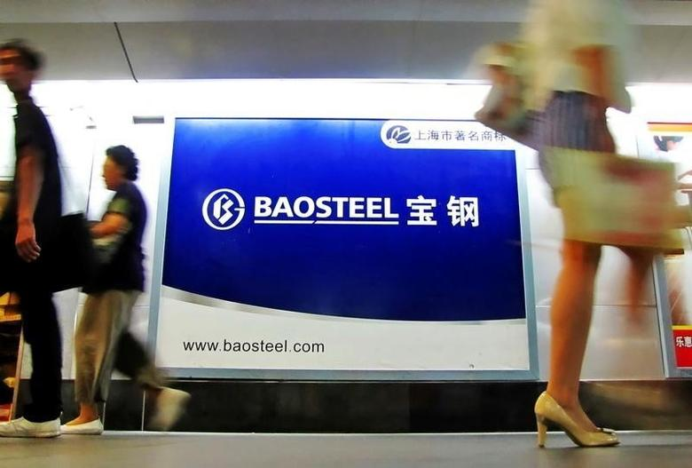 People walk past an advertising board of Baosteel Group in Shanghai, September 9, 2011. REUTERS/China Daily/File Photo