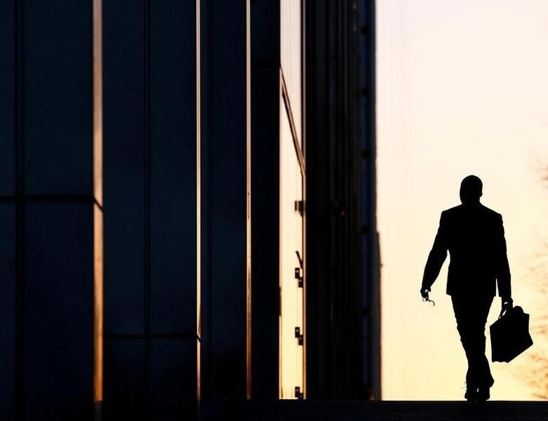 A worker arrives at his office in the Canary Wharf business district in London, Britain February 26, 2014.      REUTERS/Eddie Keogh/File Photo