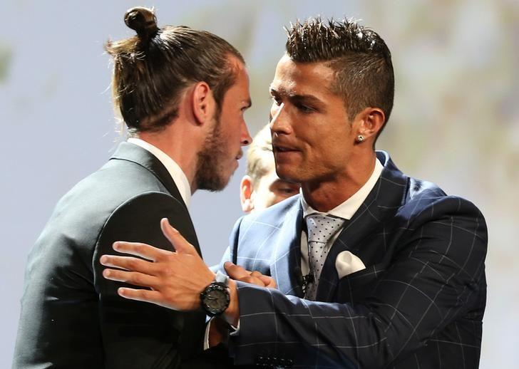 Real Madrid's Cristiano Ronaldo of Portugal (R) speaks with Gareth Bale after he received The Best Player UEFA 2015/16 Award during the draw ceremony for the 2016/2017 Champions League Cup soccer competition at Monaco's Grimaldi in Monaco, August 25, 2016. REUTERS/Eric Gaillard/File Photo