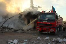 Участник гражданской обороны тушит пожар после авианалета на город Урм аль-Кубра к западу от Алеппо. Российские и сирийские воздушные силы не были причастны к авиаударам по гуманитарному конвою вблизи Алеппо в Сирии в понедельник, сообщило министерство обороны России во вторник.  REUTERS/Ammar Abdullah