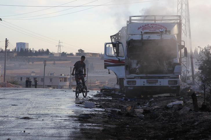 A boy rides a bicycle near a damaged aid truck after an airstrike on the rebel held Urm al-Kubra town, western Aleppo city, Syria September 20, 2016. REUTERS/Ammar Abdullah