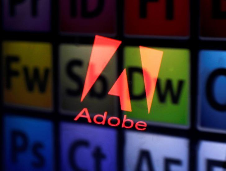 An Adobe logo and Adobe products are seen reflected on a monitor display and an iPad screen, in this picture illustration July 8, 2013. REUTERS/Dado Ruvic/Illustration/File Photo
