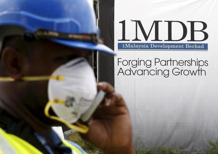 A construction worker talks on the phone in front of a 1Malaysia Development Berhad (1MDB) billboard at the Tun Razak Exchange development in Kuala Lumpur, Malaysia, in this February 3, 2016 file photo. REUTERS/Olivia Harris/Files