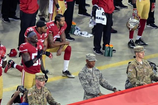 9月20日、NFLフォーティナイナーズのクォーターバック、コリン・キャパニック(写真上、左から3人目)は、試合前の国歌斉唱時に起立することを拒否したことで殺害脅迫を受けたと明かした。米カリフォルニア州サンタクララで12日撮影(2016年 ロイター/Kirby Lee-USA TODAY Sports)