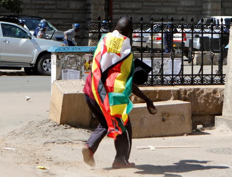 A man with a Zimbabwean flag wrapped around him throws stones at police officers during a protest against President Robert Mugabe's government's handling of the economy in Harare, Zimbabwe August 3, 2016. REUTERS/Philimon Bulawayo