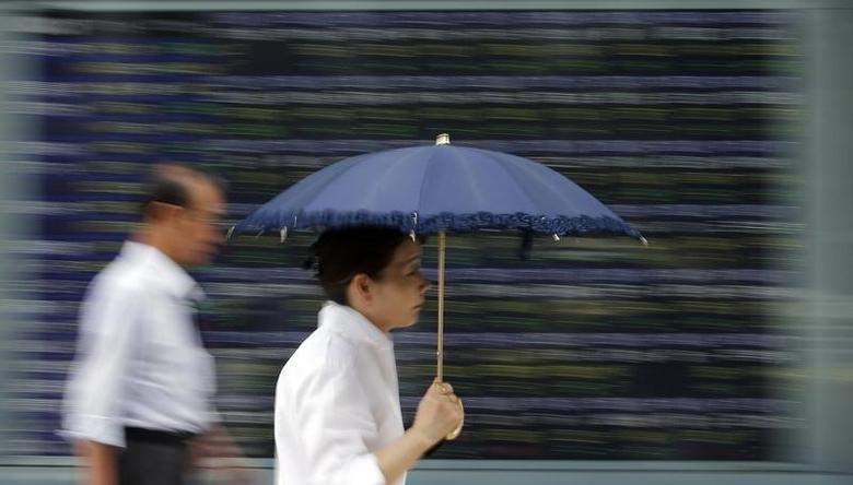 2013年7月19日,东京,一名撑伞的女子经过一家券商营业部门外的股市信息屏。REUTERS/Toru Hanai