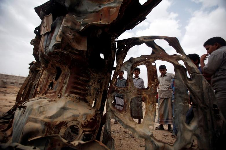 Boys gather near the wreckage of car destroyed last year by a U.S. drone air strike targeting suspected al Qaeda militants in Azan of the southeastern Yemeni province of Shabwa, February 3, 2013. REUTERS/Khaled Abdullah