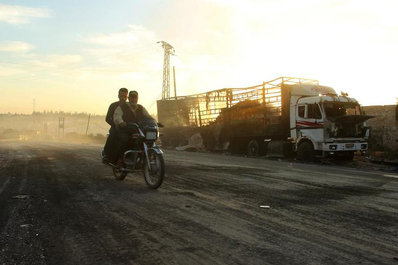Men drive a motorcycle near a damaged aid truck after an airstrike on the rebel held Urm al-Kubra town, western Aleppo city, Syria September 20, 2016.REUTERS/Ammar Abdullah