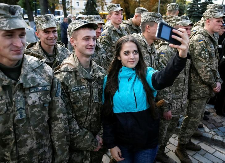 A woman takes a selfie with military cadets as they attend a Peace March to mark the International Day of Peace in Kiev, Ukraine, September 21, 2016.  REUTERS/Gleb Garanich