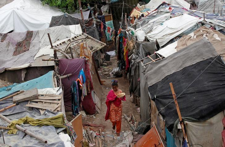 A girl carries flat bread for lunch as she walks past makeshift tents in a slum in Karachi, Pakistan July 12, 2016. REUTERS/Akhtar Soomro/Files
