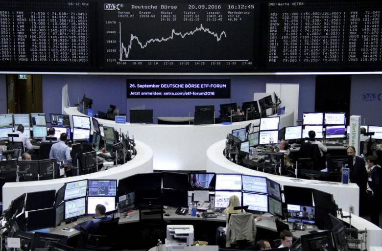 Traders work at their desks in front of the German share price index, DAX board, at the stock exchange in Frankfurt, Germany, September 20, 2016. REUTERS/Staff/Remote