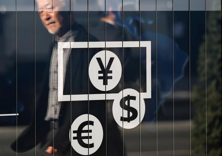 Passers-by are reflected on a signboard displaying currency signs outside a bank in Tokyo November 27, 2014.  REUTERS/Issei Kato/File Photo