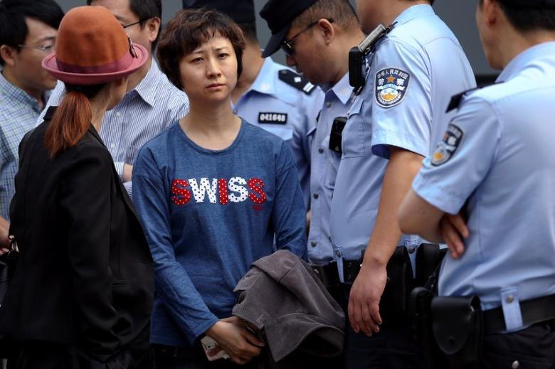Policemen stand around Lin Ru, the wife of civil rights lawyer Xia Lin near the Beijing Number 2 People's Intermediate Court after her husband was sentenced to 12 years in prison on fraud charges in Beijing, China September 22, 2016.  REUTERS/Damir Sagolj