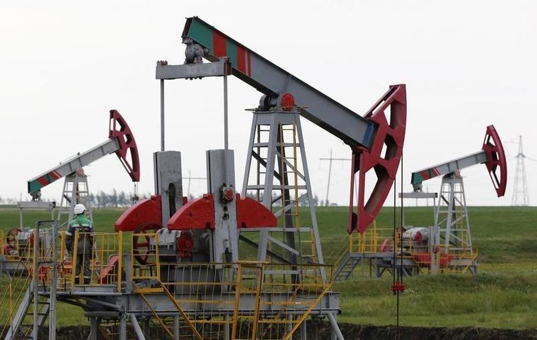 Pump jacks pump oil at an oil field Buzovyazovskoye owned by Bashneft company, north of Ufa, Bashkortostan, Russia, July 11, 2015.   REUTERS/Sergei Karpukhin/File Photo