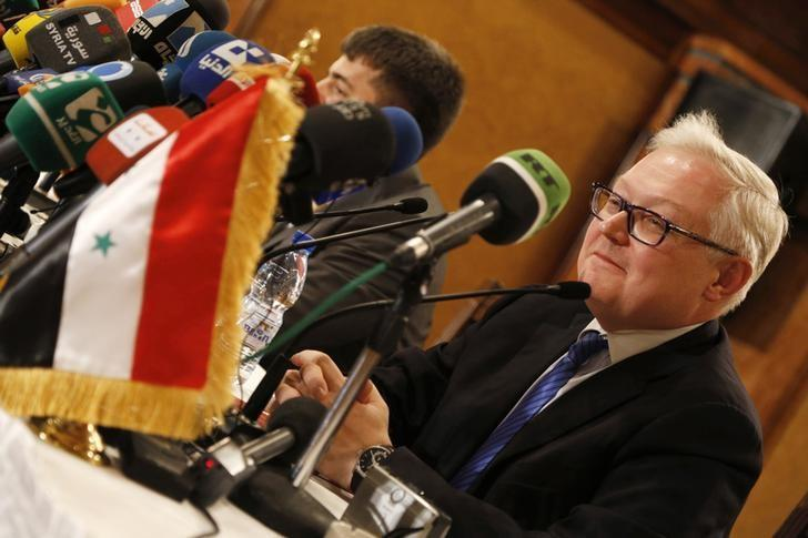 Russia's Deputy Foreign Minister Sergei Ryabkov sits near the Syrian national flag as he addresses a news conference in Damascus June 28, 2014. REUTERS/Omar Sanadiki/Files