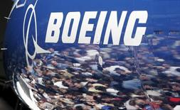 Invited guests for the world premiere of the Boeing 787 Dreamliner are reflected in the fuselage of the aircraft at the 787 assembly plant in Everett, Washington, in this July 8, 2007 file photo. REUTERS/Robert Sorbo/Files