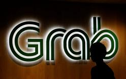 A man passes a Grab signage in their office in Singapore September 23, 2016. REUTERS/Edgar Su