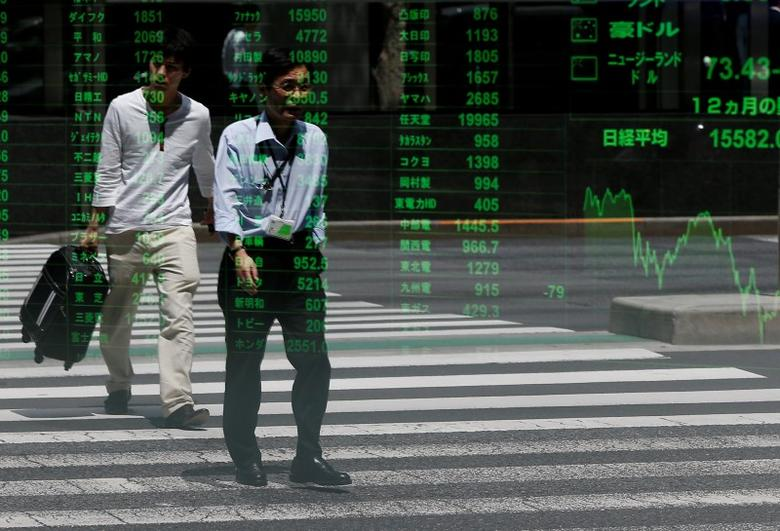 Passersby are reflected on a stock quotation board outside a brokerage in Tokyo, Japan July 11, 2016. REUTERS/Issei Kato/Files