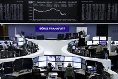 Traders work at their desks in front of the German share price index, DAX board, at the stock exchange in Frankfurt, Germany, September 21, 2016. REUTERS/Staff/Remote