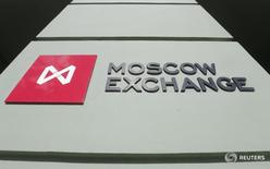 Логотип Московской биржи на её здании в Москве 14 марта 2014 года. Российские фондовые индексы в понедельник вернулись к снижению, не получив поддержки со стороны развивающихся рынков, на самочувствии которых сказались распродажи турецких активов после снижения суверенного рейтинга страны агентством  Moody's. REUTERS/Maxim Shemetov