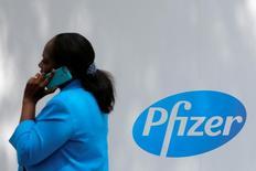 Una mujer hablando por celular pasa cerca de un logo de Pfizer, en la sede de la compañía en Manhattan, Nueva York, Estados Unidos. 1 de agosto de 2016. La farmacéutica estadounidense Pfizer Inc, que había considerado una separación en dos compañías por más de dos años, dijo el lunes que no lo hará porque no agregaría valor a sus accionistas. REUTERS/Andrew Kelly